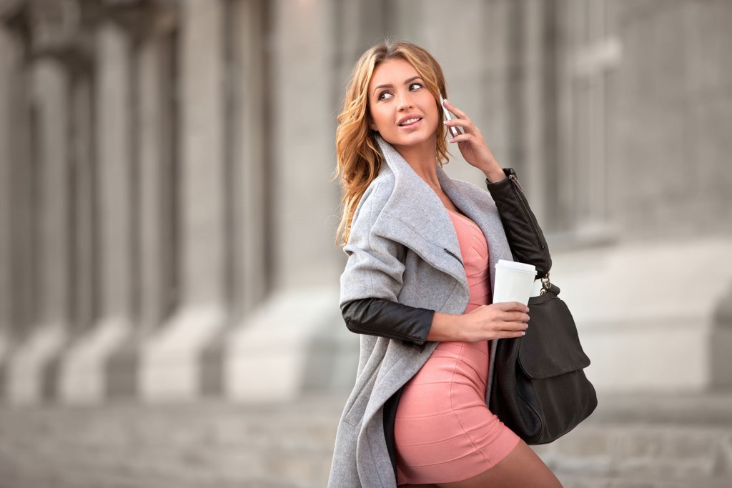 A businesswoman talking via mobile phone and holding a coffee cup against urban scene.